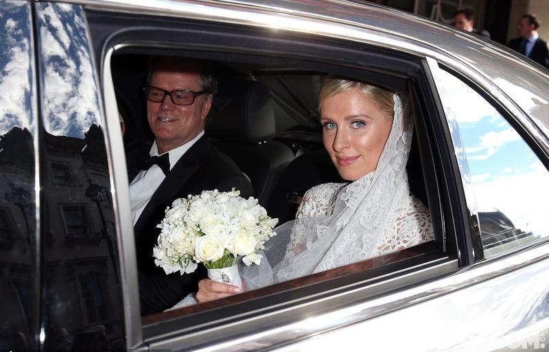31岁的新娘尼基身披价值7万5千英镑的华伦天奴特制婚纱、戴着传统蕾丝面纱、手戴一枚价值一百多万美元的8克拉钻石戒指,捧着白玫瑰从有英国王室背景的克拉里奇酒店出发,在父亲理查德·希尔顿的陪伴下乘坐宾利抵达肯辛顿宫。 新郎詹姆斯则是一袭定制深灰套装,套装和婚宴所穿的蓝色礼服均出自著名的萨维尔大街裁缝亨茨曼之手。