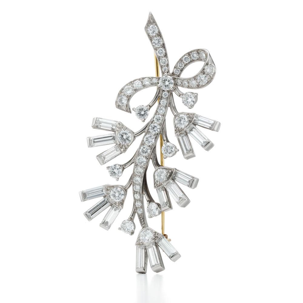 钻石花形胸针,以铺镶花瓣、长棍形钻石花茎和花朵构成花形。是蒂芙尼在1939-1940年纽约世博会期间展示了一系列密集钻石珠宝作品之一。此款胸针佩戴在女性的翻领间,取代了传统的鲜花装饰花束