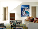 20世纪60年代的过往 流行风在这个家中随处可见,因为主人对那一时期情有独钟,而别墅的整体空间也非常适合营造那个年代的闲适情调。客厅中,两只黑色的Insula茶几来自Erik Jørgensen品牌,地毯由Atelier Zurich公司为这个家量身打造,The Rug公司制作。米色的SoftDream沙发购自Flexform,靠墙的真皮覆面酒柜购自Poltrona Frau,墙上的摄影作品出自著名摄影师Slim Aarons之手。