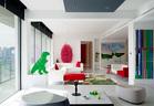 """简约的纯白空间,被星星点点的红绿亮色装扮起来,正映衬了窗外的浓浓春意。站在台阶上看客厅区域,对面走廊连接着主卧室。红白两色的组合沙发来自MDF品牌,左侧的绿色恐龙雕塑是友人送给主人家两个孩子的礼物,由隋建国创作,墙上非常吸引眼球的粉色艺术装置来自林天苗的""""一样""""系列。近处的大理石面茶几上,黑色烛台Spring是Jaime Hayon为Bosa品牌创作的,来自家天地;指南针图案的Fornasetti镀金烟灰缸来自Lane Crawford连卡佛;绿色的 Kaleido托盘为Hay品牌,来自10 Corso Como。"""