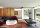 """开放的起居空间是这个家的主体,沙发Exclusif来自Ligne Roset,沙发床来自Tonic Design。近处墙上的艺术品名为""""The Battle Between Yes and No"""",是南非艺术家William Kentridge创作的丝网版画。"""