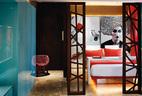 从大门看进去,海蓝色的玻璃面板从橱柜门开始沿着公寓的一侧延伸开来。右边是主卧,由装饰推拉门与客厅分隔开来。床的背后是一个夸张的黑白色Biba- esque风格人脸,印在玻璃板上。红色的椅子来自菲律宾。