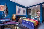 """焊接的铁艺雕塑""""Roberty 2"""",由Michel Anasse创作,来自Galerie Thomas Fritsch;床边的花瓶名为""""Spaghetti""""(意面),Gaetano Pesce设计,用黄色半透明树脂进行创作,Fish Design出品。主卧室里,仅用一面玻璃墙将睡眠区和浴室隔开,主人自己倒是很享受这种有悖章法的设计。"""