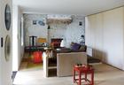 客厅中铺设着橡木地板,石灰石的粗糙墙面显示出丰富的纹理。一张中式的红漆小凳上放着来自litala的木托盘、CFOC的茶杯和一把购自Nordik Market的斯堪的纳维亚茶壶。皮革沙发NYA是Christophe Delcourt的设计,好像白色冰淇淋的纸灯Akari由Isamu Noguchi创作。角落中的灰色边桌是Paola Navone为Gervasoni设计的,桌上的部落面具来自非洲国家加蓬(Gabon)。