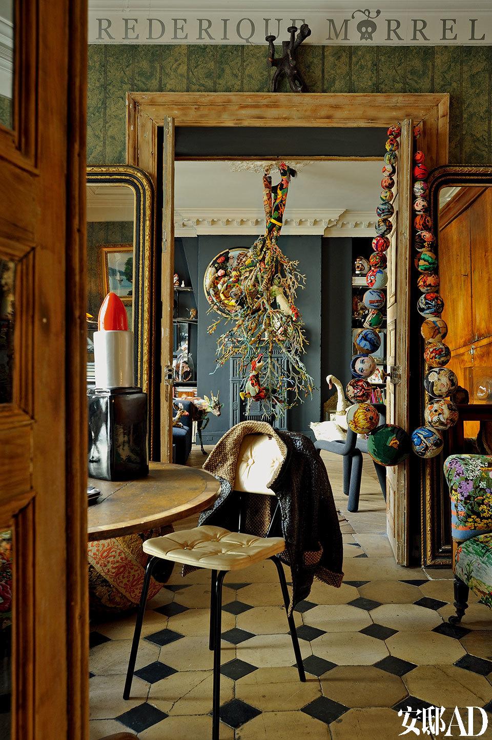 """书房与客厅相连,拉大比例的装饰品让人如坠爱丽丝的兔子洞,看到一片童话场景。紧挨着客厅的是书房,木质圆桌上摆放着一只巨大的口红模型,是女主人淘来的古董,曾经是用来做广告的展示品。右边,门框上挂着巨型串珠""""项链"""",仔细观察其表面织品,用的是一种土耳其的针织方法。"""