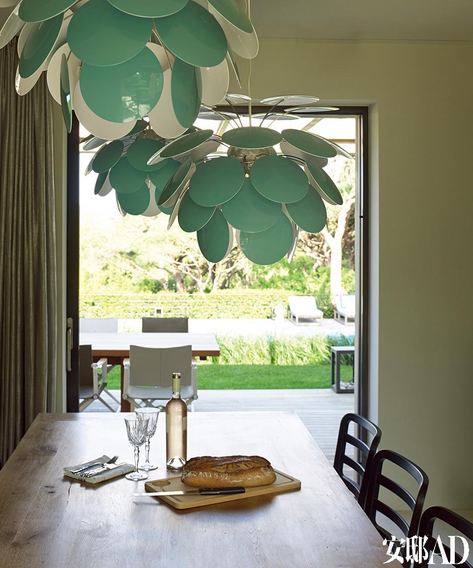 餐厅中最显眼的就是3盏由淡绿色圆片组成的Discocó吊灯,它们是Christophe为西班牙公司Marset设计的。天气晴好时,主人一家会在餐厅落地玻璃门外的露台上共进午餐。