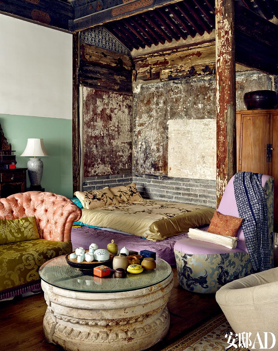 """卧床旁边的墙面残存着明代的墨竹壁画,""""每天睡在这'竹林'里 ,有读不完的书,太幸福了。""""紧挨着裸露的墙砖、剥落的墙皮的床垫,是冰逸的卧眠之处,留下这一块未经粉刷的部分,似乎能使她睡眠之时, 就和大庙的灵神融为一体。"""