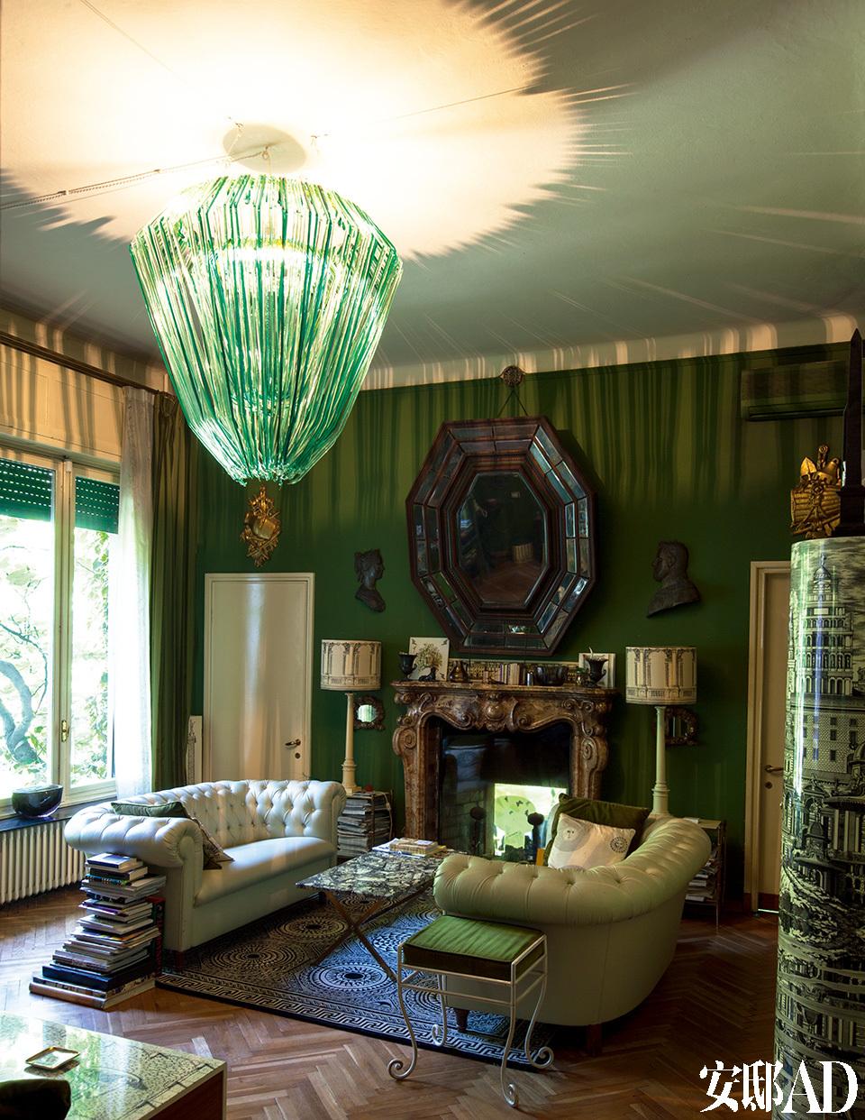 """主人对古董家具的偏爱,淋漓尽致地体现在客厅的布置上。巨型绿色玻璃吊灯,把整个房间映照得朦胧梦幻。位于房子一层的绿色客厅。客厅里的长沙发来自20世纪60年代,Fornasetti家族的羊毛小地毯""""Pavimento""""由手工编织而成,Jacopo Foggini吊灯是由Metralicato生产的。"""