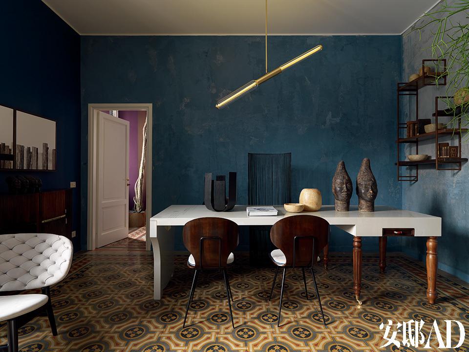 """家中着色的整体基调是由地面开始的,""""我将地板上古老的花砖看作是一幅巨型地毯,其他区域的颜色都会随之产生。""""整个家的用餐区。原有的地砖看上去像是一面巨幅地毯,这也是设计师Stefano为家中不同房间挑选颜色区间的灵感来源。他的设计师朋友们为他独家制作了这张餐桌,产品是Draga Obradovic和Aurel Basedov为Baxter制作的Typo特别款。餐桌上摆放的非洲陶土头像是Stefano的个人收藏,旁边的雪花石膏花瓶来自意大利的托斯卡纳地区,复古餐椅属于上世纪50年代,餐桌上方的金属吊灯是Pietro Russo的设计品Apollo。"""