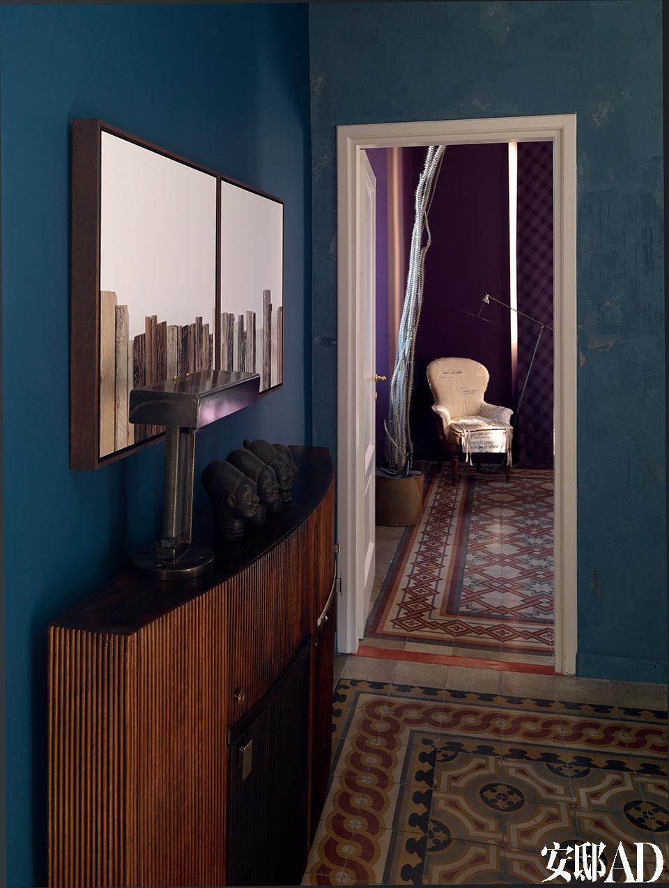 从客厅向卧室望去,质朴的地砖起到了非常关键的衔接作用,它也为墙面的用色提供了灵感。客厅木制抽屉柜上方的艺术品是由 Lorenzo Butti创作的,而柜子上摆放的台灯是Ugo Ambroggio的作品。