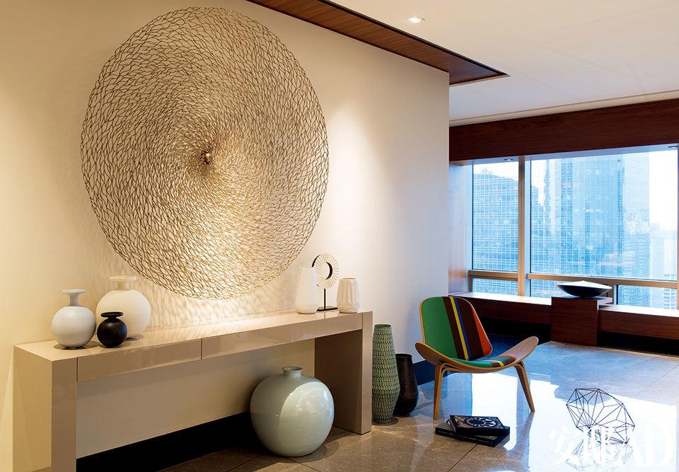 一进家门就能看到这处唯美的玄关装饰,奶油色的漆面长桌在Decca达艺家私定制,圆形的手工铜丝墙面雕塑由韩国艺术家Choi Tae Hoon打造,来自Alison Picket。桌面上的白色雕塑和地面上的钻石形摆件来自Bo Concept,CH07 Shell单人椅由Carl Hansen & Søn x Paul Smith出品,来自家天地。