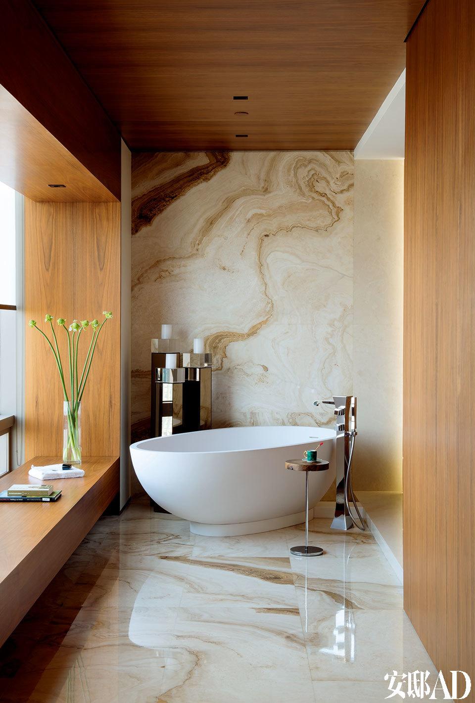 与主卧室相通的开放式浴室,Agape陶瓷浴缸由Fmarti Guixe设计,购自北京德丽堡建材商贸,金属小茶几来自Ligne Roset。宽敞的主卧室选择了中性色调,Society绿色床品来自Lane Crawford连卡佛。