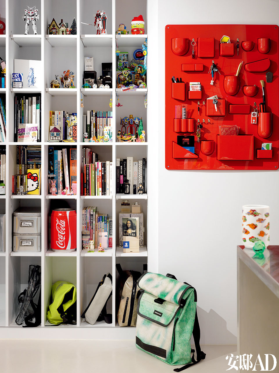 """进门处就是落地式书架,上面摆放着很多Pili从小收集的模型和高达玩具。墙上的红色工具收纳架Uten. Silo来自Vitra;右手边岛台上放着的白色龙纹图案的杯子来自Pili去年的设计作品""""漆瓷""""系列(www.utp.tw)。"""
