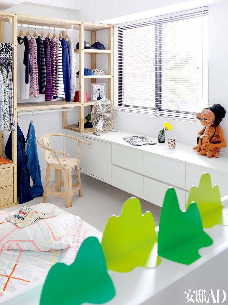 """跟大多数都市年轻人一样,Pi li的生活丰富又简单。他挑家具就像买衣服,与其买多,不如买精!主卧里的陈设很简单,木色的扶手椅正是Pili自己大名鼎鼎的设计""""圈凳""""的未上漆版本,来自Han Gallery。近景处床头上的绿色书挡就是Pili与打铁师傅们合作的设计作品""""青山""""书挡(www.utp.tw)。"""
