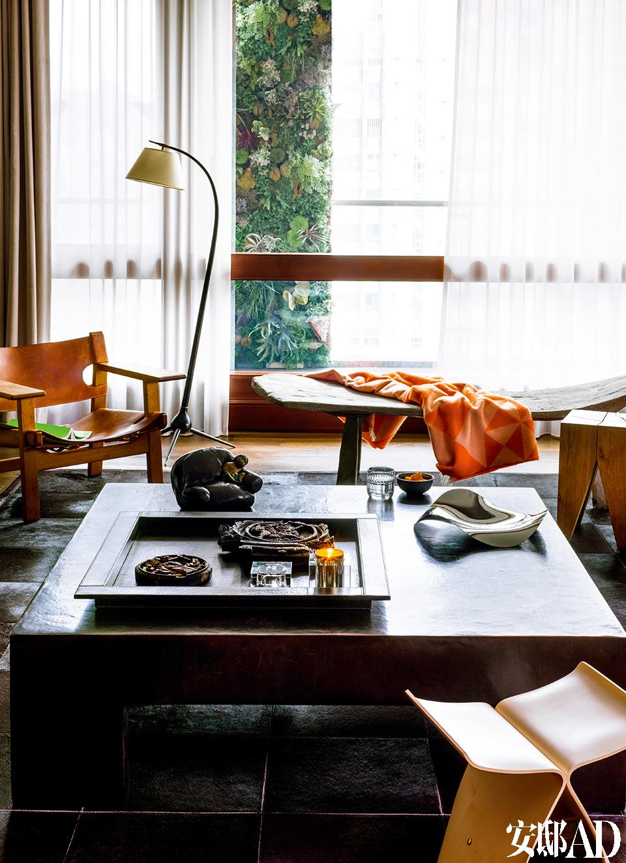 """客厅与阳台之间那张木质躺椅来自印尼,是一张老的柚木椅,因为年代过于久远,所以木质已经风化为石头一样的质感,非常特别,也是王伟忠的心头爱。柚木椅上的橘色三菱几何盖毯来自品牌Verpan、前侧是Vitra的""""蝴蝶凳"""",茶几上摆着Living Georg Jensen的""""波浪盘"""",皆由北欧橱窗提供。后侧的vintage落地灯由Severin Jr. Hansen所设计(丹麦仓库提供)。"""
