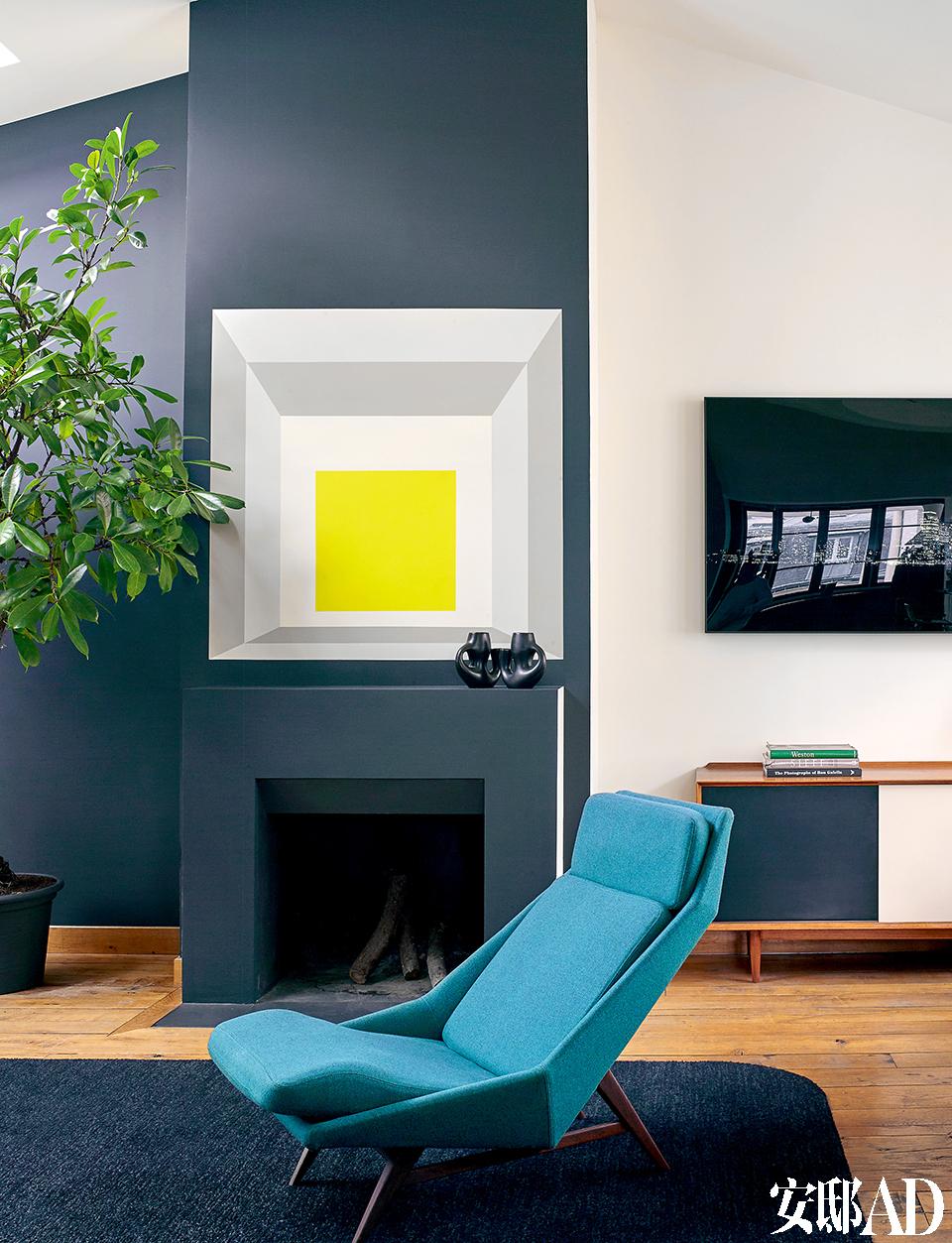 蓝色矮脚靠椅是Gio Ponti的作 品。壁炉上的两件黑色瓷器是20世纪50年代法国Revernay烧制出品的。Florence Lopez特别觅来了火车老木轨,用来铺设地板。