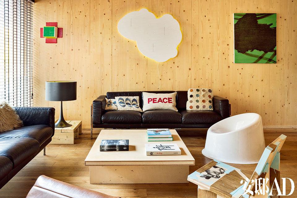 整个家完全用层压木来建造,真是一次大胆的尝试。 这种跟砖块相比更加快速和经济的建筑材料恰好也跟主人的姓氏Woods 巧妙连接。两张沙发之间的一个托垫上摆着由Sebastian Wrong设计、 Flos生产的台灯Spun Light。它上方的墙壁上挂着Jeff McMillan的纸箱画。墙壁中央挂着的是男主人Richard Woods于2014年设计的霓虹雕塑作品《Wooden Cloud(RJ)》。旁边绿色调的图画是Danny Rolph创作于1996年的画作《无题》。