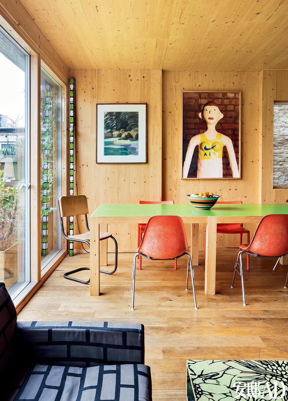 厨房里的一张木质餐桌承担起主要的服务作用,大家既可以围坐在这里吃饭,也可以闲聚聊天,把电脑搬到这里来工作也是很好的选择。在大落地窗旁的一隅竖放着Richard Woods的有光木雕作品《Wooden sculpture with light》 。雕塑旁边是Jill Spanyol 1988年的水彩画作品《Landscape》,接着的肖像画是1996年英国艺术家 Tim Steward 和 James White的作品。近处的橙色椅子是Charles 和 Ray Eames设计的School Chair,桌子的另外一头摆放着的是由Magis生产Jasper Morrison设计的Air Chair。