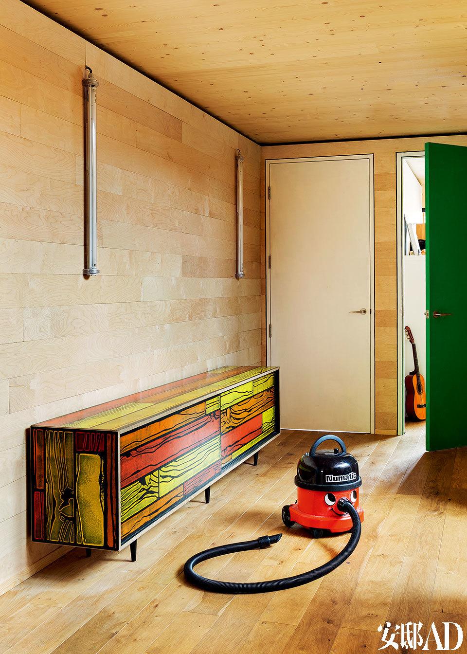 浴室所用的材料和元素都强调着工业特质,镜子里映出通向楼上的彩色木质阶梯,十分俏皮。圆形天窗则带入柔和的自然光线。
