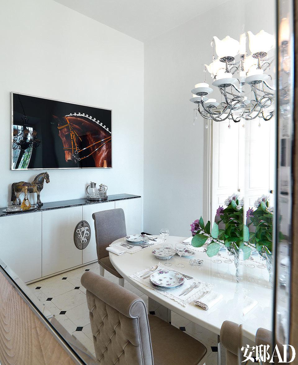 餐厅中,Esmeralda餐椅围绕着Edelbert餐桌,两件家具都是Alessandro La Spada的设计。Claudio枝形吊灯由Samuele Mazza设计,Marek餐柜是Roberto Lazzeroni的作品,以上产品均来自Visionnaire。墙上由Micheal创作的马头图案艺术品呼应着餐柜上摆放的马形雕塑。