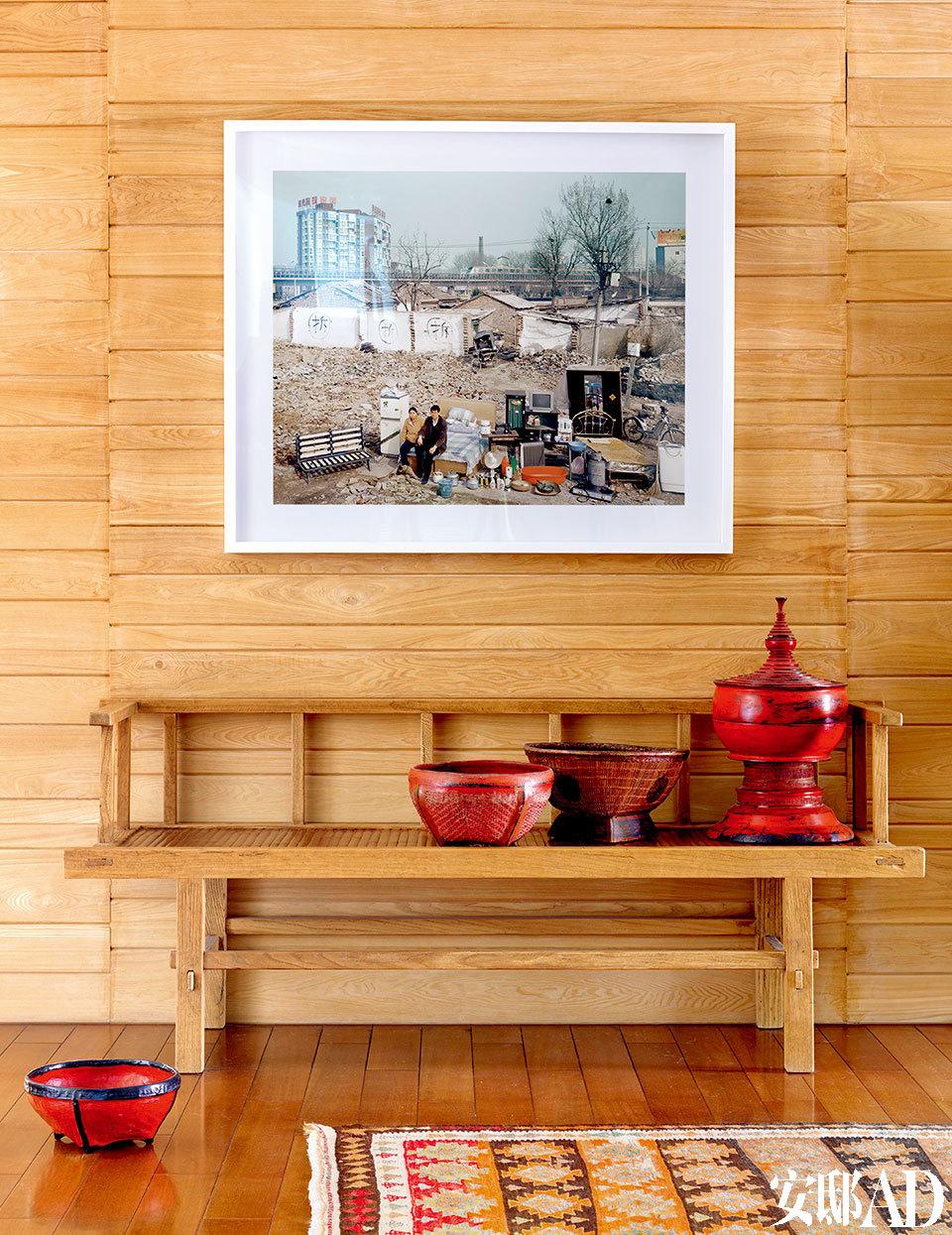 """黄庆军的《家当》,平静地展现着一个时代的标志性画面,Tanja将它摆在家里,也成了自己的一段中国记忆。入口处附近,一只中式竹质长凳来自新加坡一家专门贩售中式古董的China Collection公司,3只红色小筐和一只佛教贡盒都来自缅甸。木饰面墙上的照片是黄庆军拍摄的""""家当""""系列中的一幅作品。"""