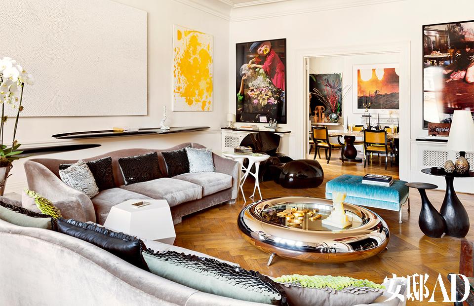 """老公寓保存完好, 无须大的改动, 家具和艺术品成了主人用来打造新家的全部 """"武器。客厅中,由Garouste & Bonetti设计的不锈钢圆桌Ring被用作茶几,沙发布面来自Manuel Cánovas,沙发上的靠垫均来自布艺设计师Ulrika Liljedahl。沙发旁的白色茶几由Mattia Bonetti设计,灵感源于口香糖,右侧绿松石色的矮凳旁,摆放着名为You & Me的蘑菇状小桌,仍然由Garouste & Bonetti出品。墙上的黄色画作出自Christopher Wool之手,白色画作是Kusama极具代表性的织物作品,画作下方是Zaha Hadid设计的隔板,门左侧的画作来自Paul McCarthy,画作前摆放着名为""""King Bonk""""的玻璃纤维脚凳组合,由Fredikson Stallard为David Gill Gallery设计于2008年。"""
