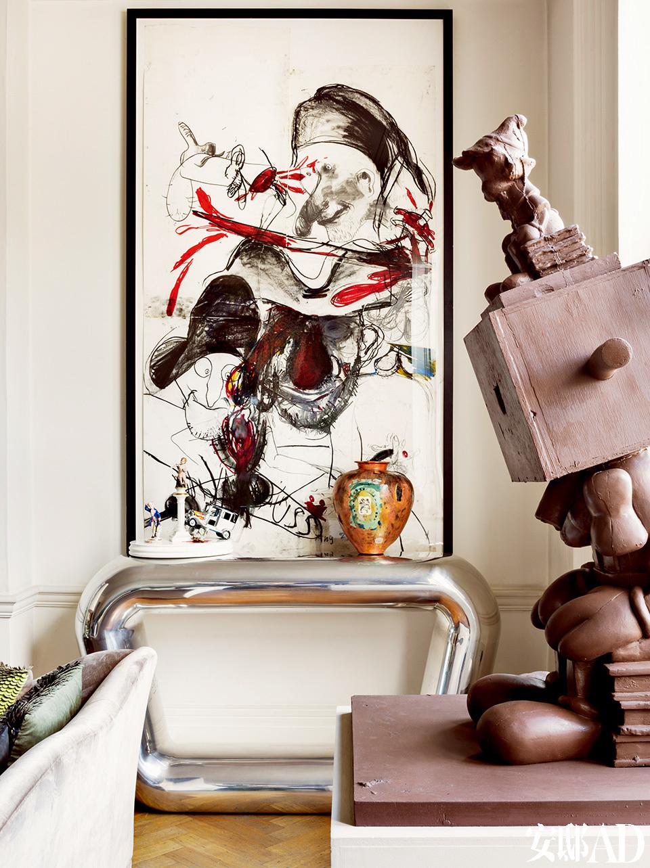 客厅一角,Mattia Bonetti设计的条案上摆着Grayson Perry 的花瓶和Barnaby Barford的雕塑作品,画作来自Paul McCarthy。