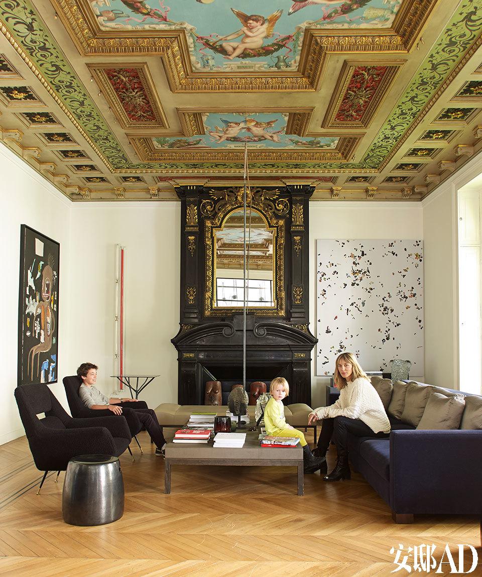 Bonstrom和她的两个孩子Victor(左)、Emil-Milo(右)坐在客厅中。当年奥斯曼男爵住在这栋房子里时,这个房间是一间音乐沙龙,也是他招待宾客的主要场所。正面墙上左侧的荧光灯管艺术装置由Dan Flavin创作于1970年,右侧的艺术品名为《Prenzlau》,是Adam McEwen在2013年用丙烯和口香糖在画布上创作的。右侧的长沙发为定制品,左后方的边几Hogweed来自Weiki Somers在2010年出品的Frozen in Time系列。