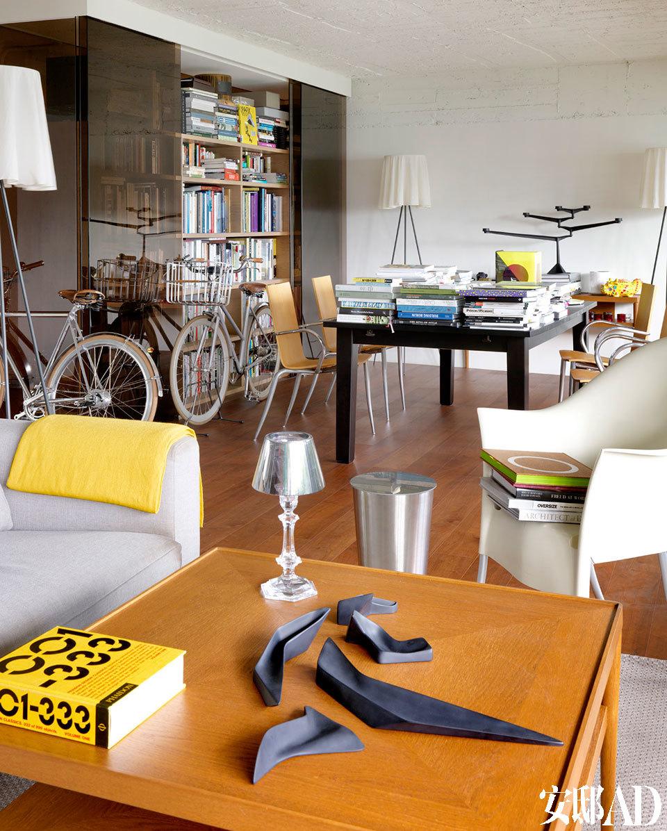 门口的书架作为挡风水之用,加上前面的书桌,为其海量藏书妥妥地安排好栖身之地。餐桌同样摆满各种书籍,木色单椅为Philippe Starck早期的作品《Olly Tango》。