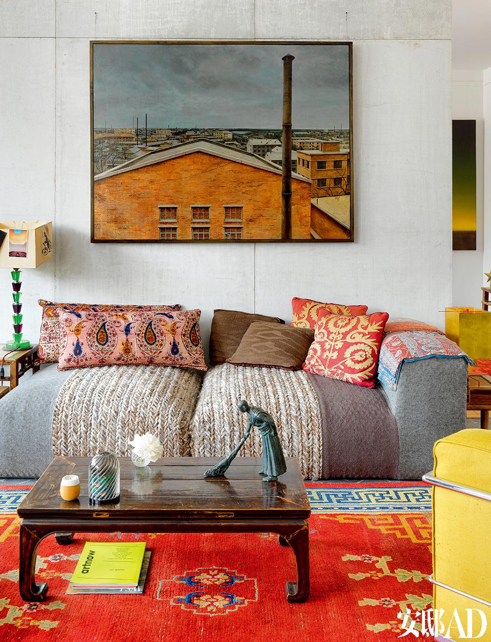 起居室墙上的油画是艺术家艾安的作品。茶几上的小型人像雕塑来自王书刚。客厅的地毯来自西藏。