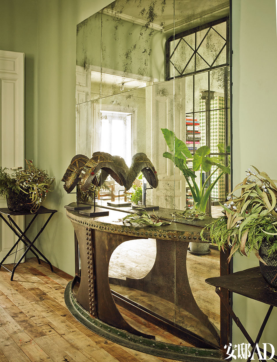 进门处,摆放着由旧长椅改造而成的铁制桌台,购自巴黎一家古董店。桌台上摆放着喀麦隆面具。做旧的镜子来自De Robles。一对简易小桌来自马德里丽池公园(Parque del Retiro)。