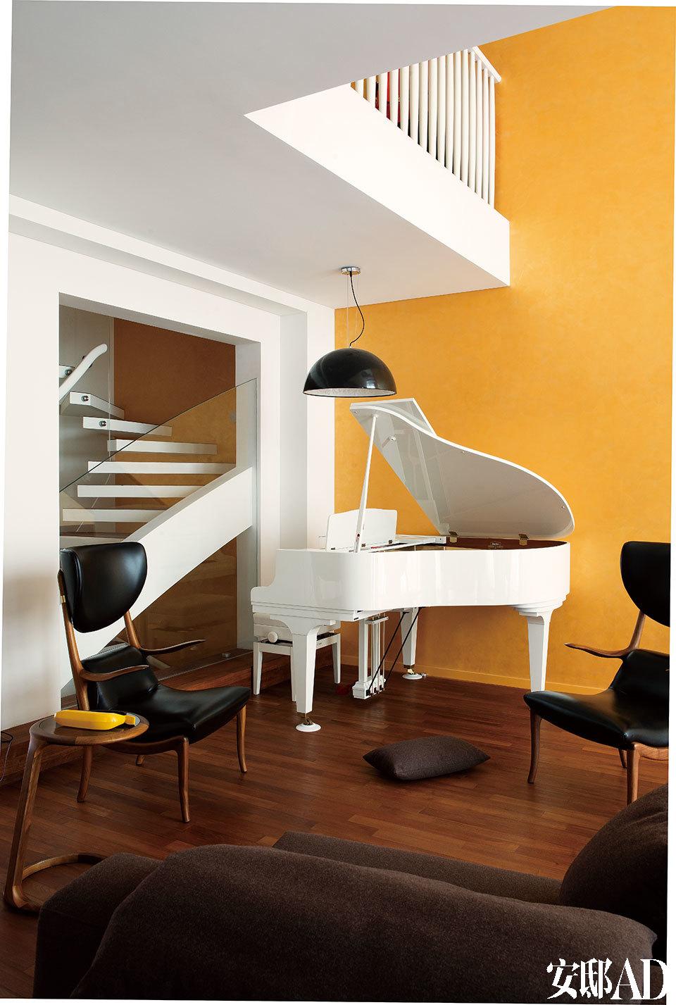 客厅的另一侧是沙发和娱乐区,一整面墙壁被喷涂了金色的马来漆,钢琴上的弧线与后面的楼梯形态非常协调。楼梯旁的这面墙壁彼时还是一堵实墙,导致楼梯处非 常昏暗,家人常常在此跌跤。设计师Arnd将它打通,安装上钢化玻璃作为护栏,阳光从此倾泻进去。这处大改动既美观又实用。白色的三角钢琴与墙面及新修的楼梯在形态与色彩上都完美契合,连钢琴上方的吊灯都为搭配琴键而选择了亮光黑。