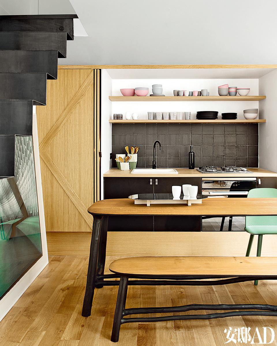 """橡木门一拉开就能看到整个厨房。在楼梯下面,有一幅Matthieu Salvaing拍摄的照 片(来自Downtown工作室)。餐台上放置着Camille Flammarion式的""""Modules """"壶,桌 上则放着由Nicolas Le Moigne设计的""""Narcis""""托盘(来自Nextlevel工作室)和由Mud Australia设计的碗碟(来自Sentou)。"""