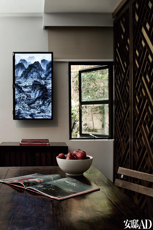 """用餐区,黑色铁质窗框为定制品,手工感极强。榆木餐桌是源自19世纪的古董家具,靠窗的墙面上挂着中国艺术家杨泳梁的数码山水作品,创造了一处另类的风景,与小窗外的实景形成对照。""""拥有绿色窗景对我来说尤为重要,窗外的清晨能让我暂时忘却身处香港这座钢筋水泥作森林的人工之城。"""""""