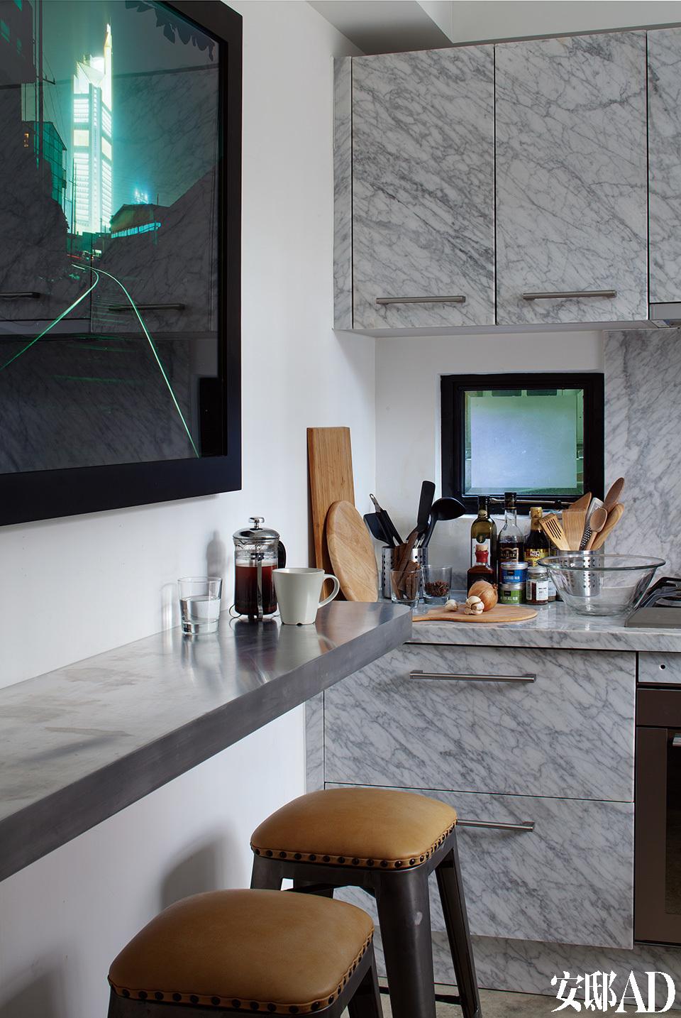 厨房的定制整体橱柜使用了意大利大理石材质,带来一点奢华之感。侧墙上挂的是蒋鹏奕的摄影作品《发光体》。全套定制的浅色大理石面整体橱柜,打造了高品质的厨房,热爱美食的意大利人必然珍视这样一处空间。