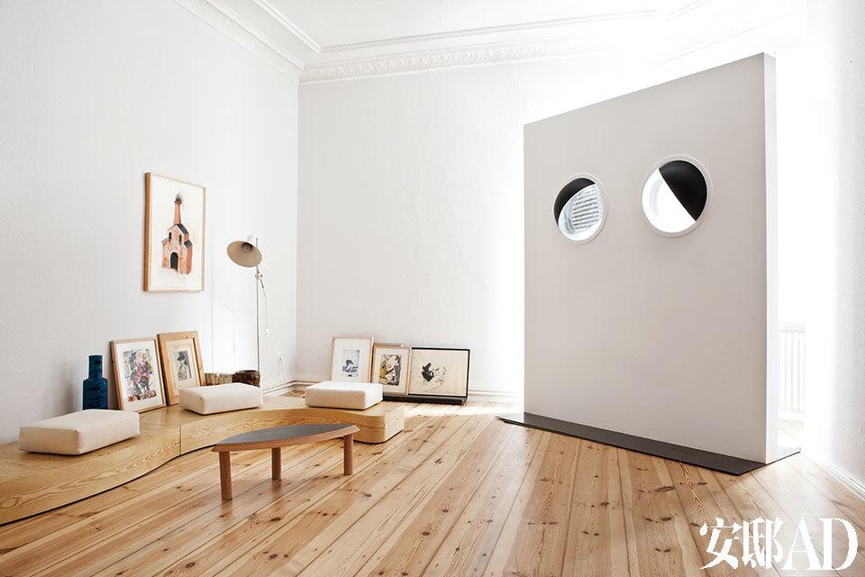 """由Uri Tzaig用木材和有机玻璃创作于1997年的Moon Eye Window仿佛一堵隔墙,正好放在窗前,让人通过月球般鼓起的""""眼睛""""来看窗外。地面上摆着Janette Laverrière设计的家具和来自Johannes Kahrs的一些画作。"""