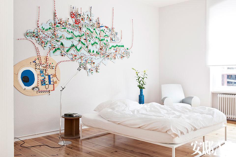 """卧室的墙面上装饰着 Nathan Carter的作品,由胶合板、线材制成,再用墨水画上图案。床边的扶手椅由Philippe Starck设计,床头桌和餐厅里的坐凳一样,由Liam Gillick设计,床来自Cappellini品牌。""""每当我想要看清这墙上的' 路线' ,它们就仿佛总在变幻,躲闪着我的眼睛。"""""""