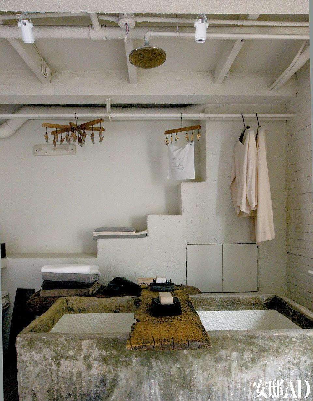 浴室中,一座从农村收来的盛水石槽,经过简单抛光和油漆,就成了非常酷的浴盆,顶部还特意安装了花洒。搭在浴盆边沿上的一块木板承载了手工的木质皂盒,里 面是手工的植物洁面皂、浴皂。厂房中原有的管道顺理成章被用作了晾衣杆,上面挂着带夹子的木质晾衣架。以上物品以及图中的睡衣、 纯棉浴巾均是无用的产品。朴素的石质浴缸简直能媲美意大利设计、轻轻的几件素衣仿佛照见了那位生活简单却精致的女子。