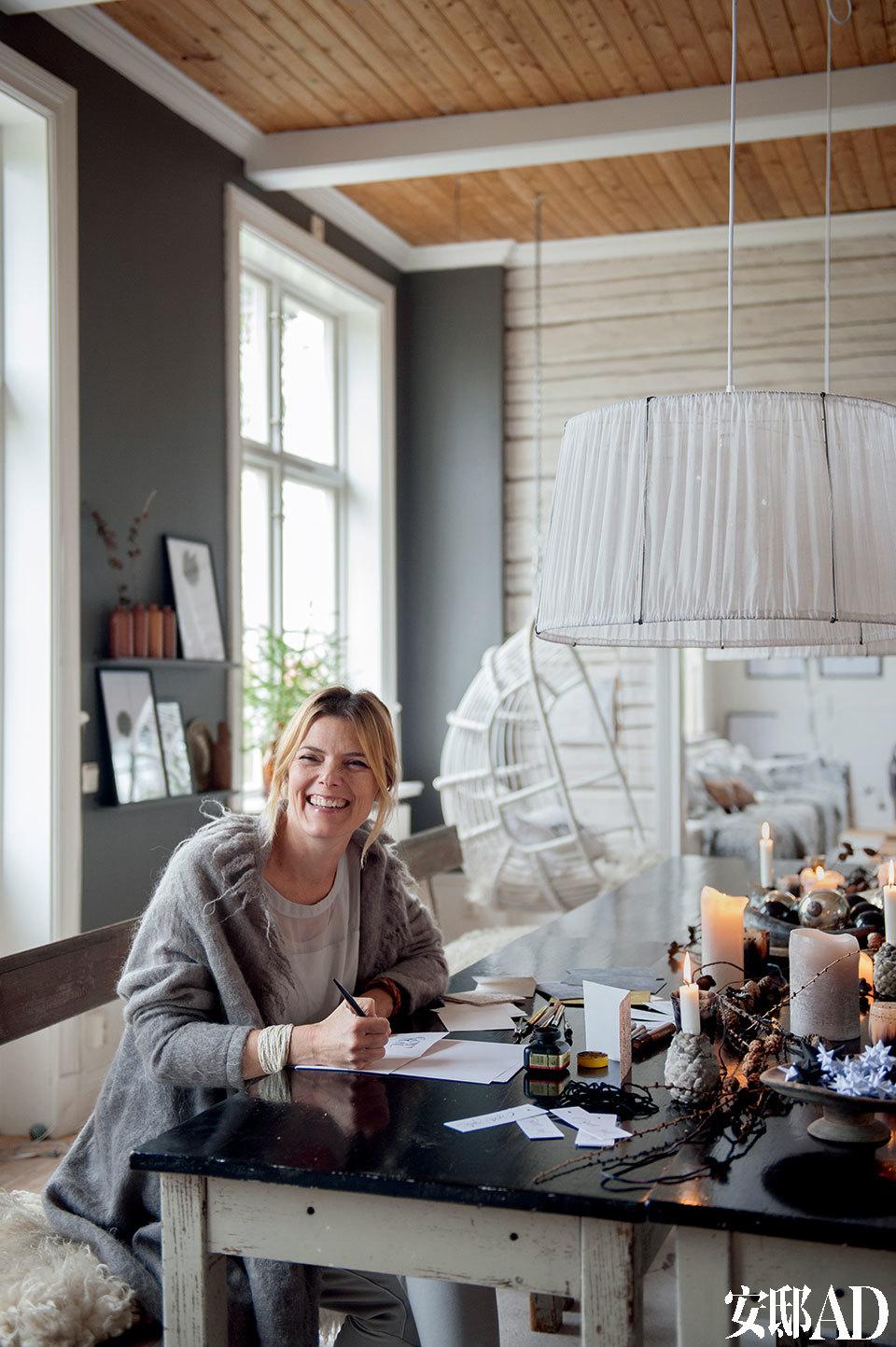 女主人Ylva开心地在餐桌上为圣诞礼物题字,她常在这里创作各种手工和艺术品。 主人:Ylva Skarp,设计师兼书法家,擅长在礼物上优雅地题字。在全世界的零售范围内,从靠枕到陶器的各种商品上,都有她创作的艺术字母。丈夫Daniel,瑞典运输管理部门的销售经理。夫妇二人与他们可爱的孩子:14岁的Hugo、11岁的Vega,还有Siri和Karla这2只猫咪,以及4只母鸡、1只公鸡共同生活在瑞典西莲湖(Lake Siljan,瑞典中南部的湖泊,面积达354平方公里,世界著名旅游地)的旧校舍里,这是一座310平方米的前校舍,在Leksand郊外,建于1901年。