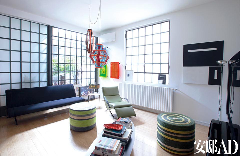 """艺术品和设计单品""""霸占""""着整个起居空间,Marconi说家里的艺术品大多是他从拍卖会上""""抢""""回来的,或者在寻找新艺术家时,顺手带回来的。起居室的右墙上挂着André Butzer的油画,用尼龙绳扣牵引的吊灯是艺术家Tobias Rehberger的作品,木椅上绘着Amelie Von Wulffen 的彩色水粉画,Toio地灯出自Flos,躺椅和沙发来自Osvaldo Borsani,前方的矮桌出自Charles & Ray Eames ,角落处的有机玻璃作品出自艺术家Kerstin Brätsch。"""
