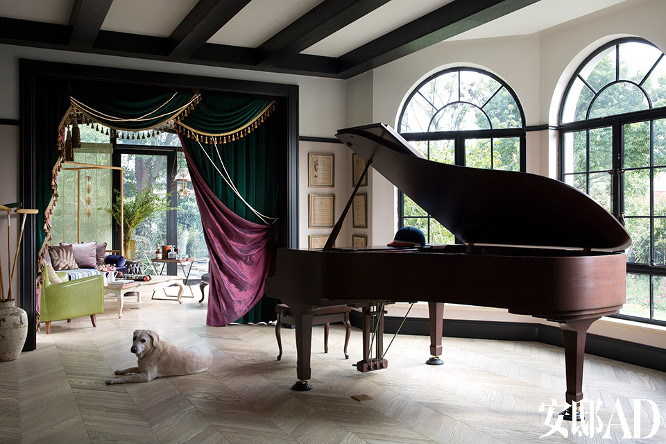 """进门右手的空间,是被规划为""""看""""的空间之一,放置了主人收藏的一架纪念版雅马哈演奏钢琴。门帘由设计师小贝亲自设计监督制造,营造了一个戏剧舞台的效果。"""