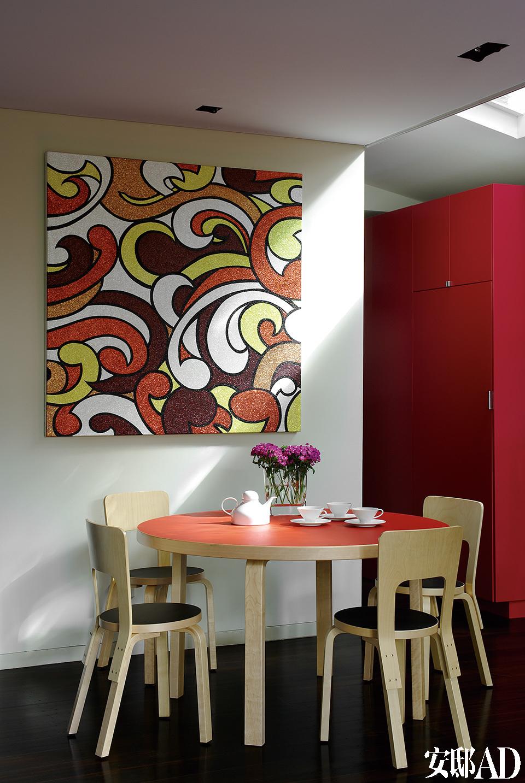 """厨房边的简餐区设置了Artek的餐桌和65餐椅,名为""""A Bed Of Colour To Squeeze Between a Sidewalk Crack""""的挂画基于新西兰毛利人的文化创作,作者是Reuben Paterson。"""