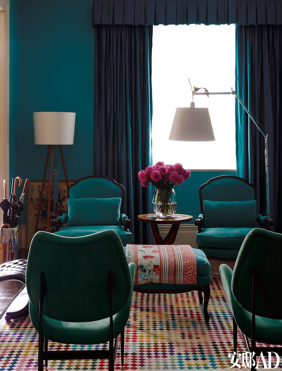 客厅中,近处Grant Featherston的1960 Scape椅与对面孔雀蓝的Sensuede路易十五风格扶手椅相映成趣,一旁是Artemide Tolomeo的阅读灯,像素化的亮色地毯在Living Art Gallery定制。