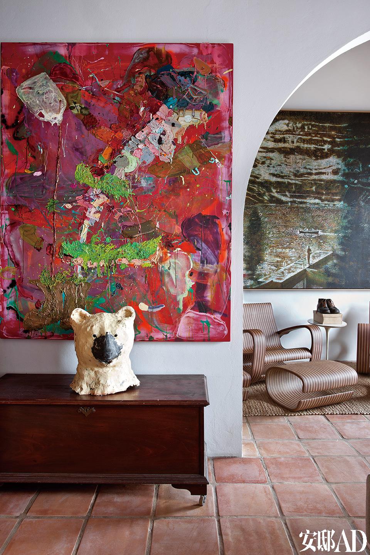 """卧室内挂有Angel Otero的红色画作,熊头形状艺术品来自Anne Chu。右侧是Peter Doig的画作。 """"因为这些作品的创造者彼此也是很好的朋友,我们收藏的作品之间存在着一种和谐共鸣,这正体现了一种友谊的精髓。"""""""