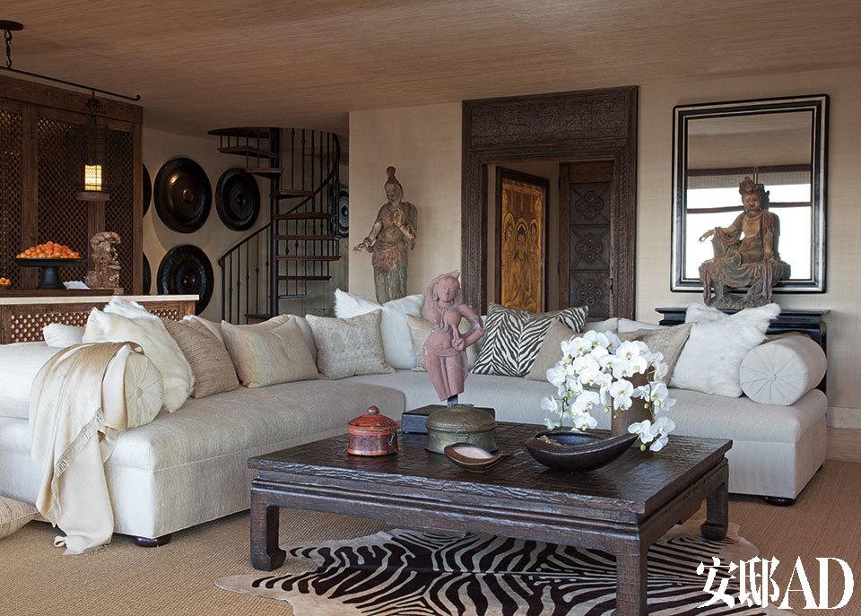 """对雪儿来说,各式佛像不仅是装饰,更是信仰所在。而米白色、象牙色等中性色又为空间注入了一股现代都市感,恰好平衡了过强的异域风情。 Martyn为雪儿的主起居室设计的舒适沙发让她能够在那里放松心情并欣赏洛杉矶的美景。""""她不要色彩斑斓的设计,于是我们选用了奶油色、白色、象牙色与深棕色来营造视觉的冲击感。""""沙发面料来自Kravet,斑马纹小地毯来自Edelman,海草地毯来自Stark。"""