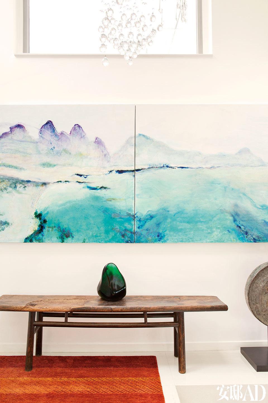 """门厅中女主人的画作,技法源于欧洲,意韵却近似于中国的水墨。门厅中悬挂着由女主人Tracy 创作的""""戛纳1964"""",这是一幅描绘法国南部山海相接美景的画作。下方年过百岁的旧长凳来自一家西藏的寺院,购于香港荷李活道上的Arch Angel古董店。长凳上摆放着一块质感十足的绿色黑曜石(天然琉璃),出产于火山众多的爪哇岛,主人购自新加坡的Pagoda House古董店。"""