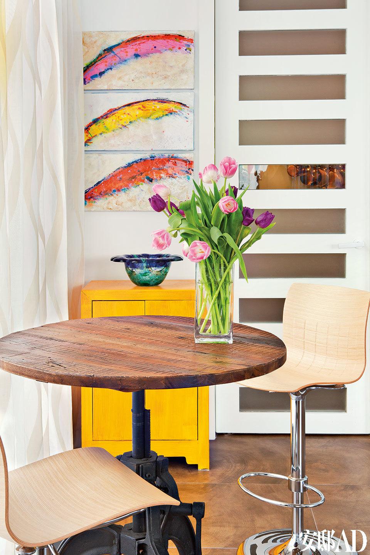 """唱歌、画画、专业的寿司厨师……女主人的生活异常活跃,家中则更需要安静喘息的角落。厨房外一个充满阳光的角落被放置了一张咖啡桌,这里是清晨喝咖啡的最佳位置。木桌来自香港的Aluminium,黄色中式小柜上方悬挂着Tracy创作的三联画""""翅膀(Wings)""""。"""