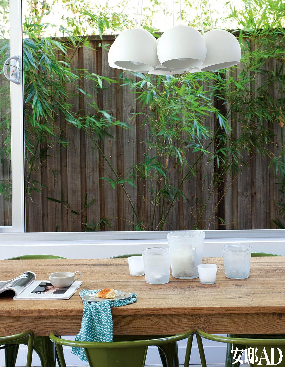 用餐区紧靠一大面窗户,窗外的绿竹摇曳,让进餐成为一件极风雅的事。餐桌来自The Willmott Collection(info@thewillmottcollection.com.au),是手工定制的再生法国橡木法式农舍餐桌。