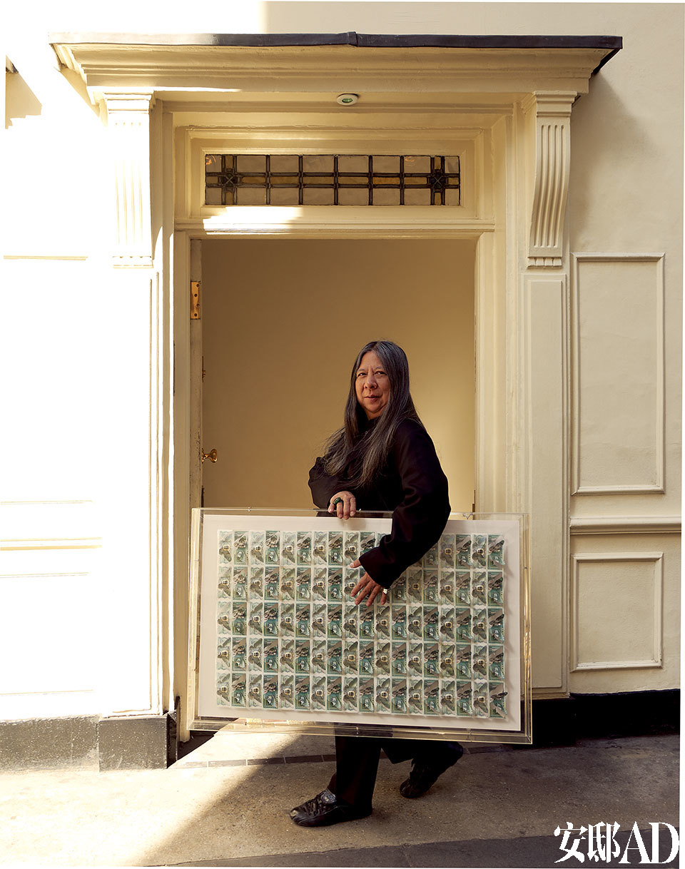 John Rocha手持Justine Smith的作品站在自己的公寓门口。