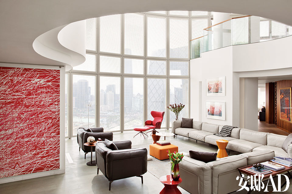位于二层的客厅是男主人精心设计的区域,大气的皮质沙发来自锐驰,因为空间大,就多定了几组。近处的渐变红色玻璃花瓶和沙发椅背上搭的黑白小毯来自BoConcept北欧风情。放花瓶的红色茶几和远处的黄色茶几,品牌均为Minotti,来自家天地。靠窗处的红色躺椅和脚凳,品牌为BD,来自家天地。中间的橘色脚凳,品牌为Minotti,来自家天地。墙上的红色画作出自徐若涛之手。